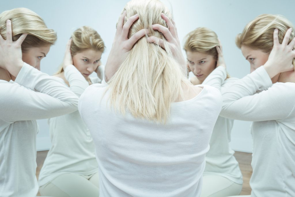 Anxious young woman in white surrounded by her alter egos