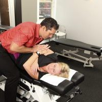 Chiropractor adjusting a female patients neck on a chiropractic bench